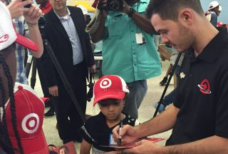 Kyle Larson signs an autograph for a child at the Salvation Army Boys and Girls Club on Wednesday. Larson and Target presented the Charlotte, North Carolina, club with toys. (Photo: Dustin Long)